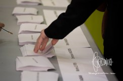 A person picks a piece of paper for voting.