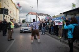 Man in traditional Bavarian clothing waving flag on street