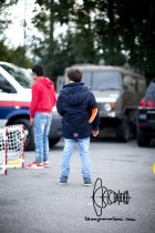 Children play hockey to distract themselves from the situation. Military and police cars parked right next to them.