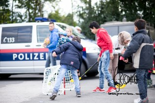 Children play hockey to distract themselves from the situation. Police watches.