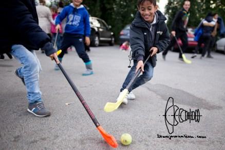 A Syrian refugee boy playing hockey.