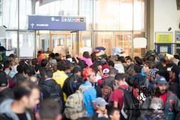 Hundreds of refugees push through narrow doorway.