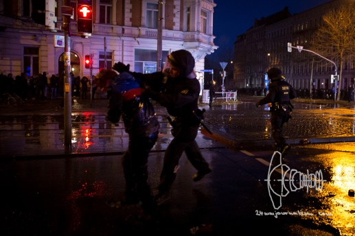 A riot police force officer punches a man that was sprayed by a water cannon only seconds earlier.