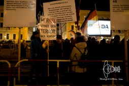 PEGIDA board member Birgit Weißmann holding up a sign stating that chancellor Merkel brings terror into Germany.