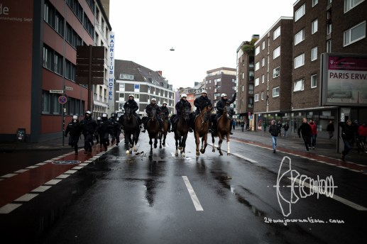 Police on horses galop to counter protes.