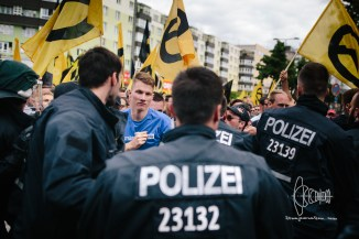 Up-front: Members of the Bavarian Identitarian Movement, such as Paul Z. in the left of the picture - raising his fist towards police.