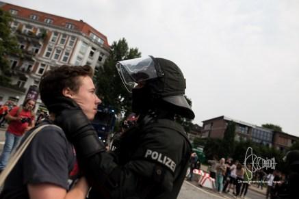 Roadblock close to ICC - Policeman pulls protestor ar throat