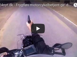 betjent på motorcykel affyrer skud