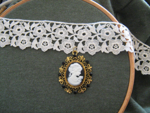 17 and a half inch / 44.5 centimetre vintage lace ribbon choker with gold plate fastenings, goldtone setting, black matte rhinestones, and a resin cameo.This unique dainty necklace is perfect for Classic or Sweet Lolitas, or anyone with an affinity for lace and cameos. The soft lace choker is easy on the skin and will sit just as well as a loose necklace over high-necked clothing as a choker on the wider neck.[here]