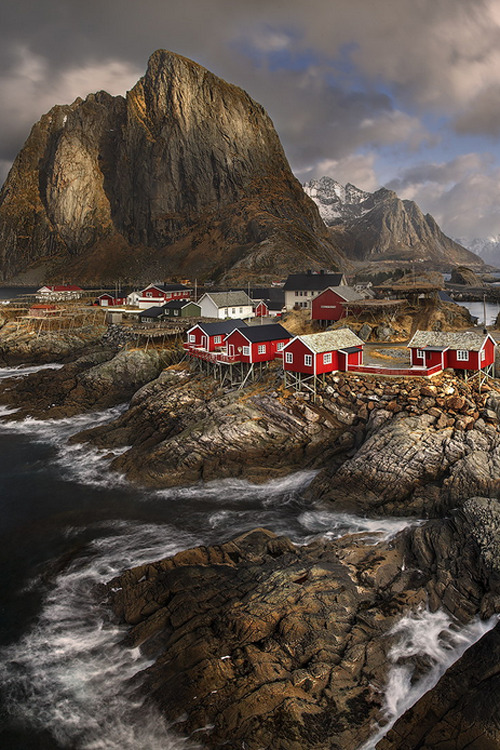 atraversso:</p> <p>Norway  by Yury Pustovoy</p> <p>BRIGHT SPOT IN THE DARKNESS<br /> Amidst the raging waves of the oceans,<br /> thrashing against the jagged rocks,<br /> sit pretty red houses on their tall sticks,<br /> prepared to weather the worst storms and<br /> whatever nature might throw them.<br /> Stand strong!