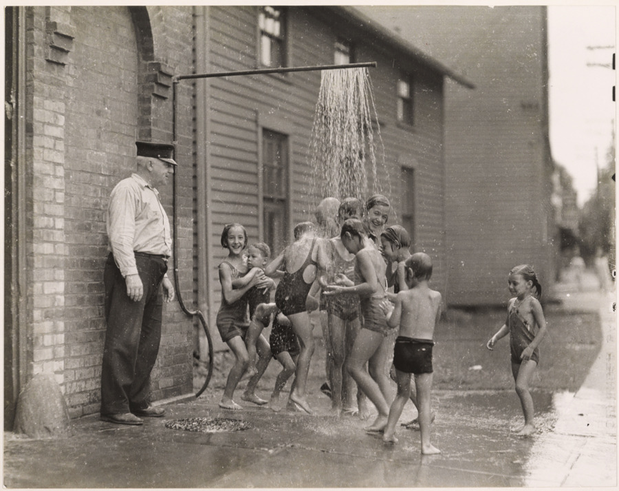 Children cool off from summer heat outside a Connecticut firehouse, April 1935.Photograph by Luis Marden, National Geographic