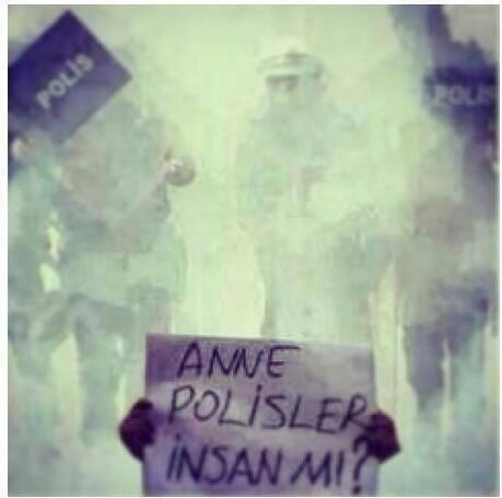 """A demonstrator under a cloud of tear gas holds a sign that says """"Mother, is the police even human?"""""""