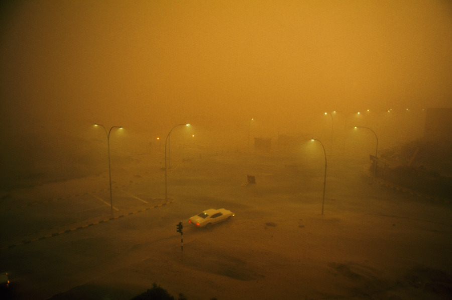 A combination sand and rain storm batters a lone automobile in Kuwait, May 1969.Photograph by David Cupp, National Geographic