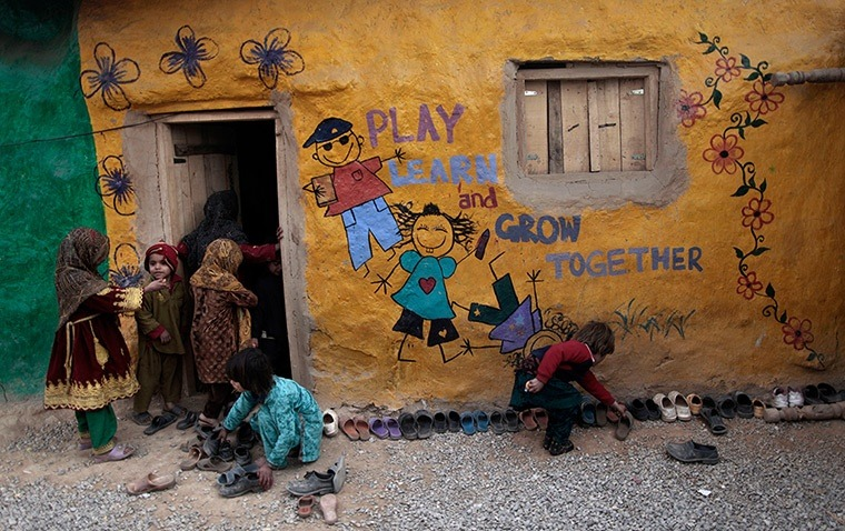 Islamabad, Pakistan: Displaced schoolchildren look for their shoes while others enter their classroomPhotograph: Muhammed Muheisen/AP
