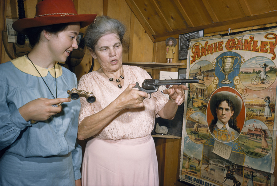 Annie Oakley's niece shows off mementos to woman costumed as Annie in Greenville, Ohio, April 1955.Photograph by Bates Littlehales, National Geographic