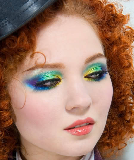 "Hello! Today I'm going to be showing you how to achieve this look. (Just the eyes.) It may seem difficult, but it's really not. Obviously this isn't an everyday look, but for parties (Maybe New Year's parties?) it's really fun! Things you'll need: Range of eyeshadow colors including: Purple, blue, green, and yellow. (You're probably going to want different shades of each color) I find that it's best to use a palette for these types of looks. A great one that I use nearly everyday is the Coastal Scents 88 Piece, which you can find here: http://www.coastalscents.com/cfwebstore/index.cfm/product/1677_122/88-piece-makeup-palette.cfm It's a pretty inexpensive palette, the colors are vibrant, and the shadow applies smoothly. Black eyeliner- I'd use gel for this, but pencil or liquid work just as well. False lashes (Optional) Eyeshadow brushes… This is important! Don't use the pads to put on your eyeshadow. They don't work as well, you won't get very vibrant color, and they scratch your skin. Your eyelids are sensitive, so you don't want to put weird things on them! A blending brush. These are generally big, puffy versions of eyeshadow brushes. If you don't have one, an eyeshadow brush will work okay. Let's start! Put primer on. This will hold your color better and the colors will show up much brighter. We're going to start from the inner eye. (The part of your eyelid that is closest to the bridge of your nose.) Sweep a bright yellow on the top AND bottom of your eyes, covering about 1/3 of your eyes. (When I say eyes, I mean your upper lid and your lower lid, where you'd normally put eyeliner on on the bottom.)  Take a light teal-green (I think it looks similar to Ariel's fins. FYI- She's the Little Mermaid.) and sweep it from about 3/4 of the way down on the yellow and finish of half of your eyes. Remember, we're going from right to left. Take a brighter green and go over nearly all of the light teal and bring it towards the end of your eyes. Remember, you're blending all of these colors together as you're doing it. You don't want hard lines. Using a royal blue, apply a small amount on the outer corner of the upper lid. This will be the least used color on the upper lid. Using the same royal blue, apply a large amount on the lower lid, tapering out about two centimeters and up. On your upper lid, taper a navy blue, but go starting in the middle of your crease. (The part where below your eyebrow bone where the skin indents.) Finish the colors off by brushing a bright purple at the ends and tapering it out, making a ""V"" shape that should be colored in. Next, we're going to add eyeliner. I'll add three separate tutorials for gel, liquid, and pencil liner. So just scroll down a bit more to find them, and come back up here when you're done! (Some of you might know how to do this, so you can skip this step.) Adding false lashes- OPTIONAL. If you're not adding false lashes, skip to the next step. I'd suggest having someone else put these on or just not doing them if don't feel comfortable putting them on. I always get asked if they hurt. The answer is no. Although- don't open your eyes when you first put them down. If the glue gets in your eyes, it burns! Now I'm assuming you have your lashes, as well as lash glue. Some lashes come with tiny bottles of glue. Don't use that. It doesn't work well. I like Sephora's lash glue. It's inexpensive. It's called ""Duo"" I believe. Now to begin. Take a lash and notice which side is longer. The side that's longer with go on your outer eye and the shorter will go on your inner eye. (You should've figured out the latter if you read the first part of the sentence.) Squeeze a THIN line of lash glue (Quick note: Elmer's won't work. I'm serious. People have asked me before.) onto the eyelash strip. Blow on it for thirty-fourty seconds while it dries a bit, becoming tacky. Then, close your eye and put the lash on trying push it as far back and as far down as you can so it's the closest to your lash. It probably won't come out perfect if you're not used to doing them. They can be frustrating. Open your eye and wait a bit. While you're waiting, do the other eye. I like waiting about ten minutes to make sure they're fully dried. If you mess with them before they're dry, it's disaster. Let's pretend your ten minute chill-fest is over. Using a lash curler, now I know this next part is just shocking, curl your lashes. This will make them look more natural and get them to mix in with your natural lashes better. Here is what a lash looks like when applied in an alright manner- (I'm not an expert.)This does have mascara on it too, though. Mascara time! Most of you probably know how to put on mascara, it's really not that difficult. But a few things you might want to know is that when you're putting on layers, there are ways to do it. Makeup artists differ in the brush size to begin and end with, so you can find your own medium, but I'm going to tell you my favorite. I start with a brush that has a lot of thin bristles. Next, I move onto my thin, short, bristled brush. I finish off with a thick bristled brush. It's really up to you what you'd like. Your look is complete! This might not turn out the way you want it right away. But keep practicing and you'll figure it out. Eyeliner tutorials: Gel Remember to use a brush for this.  Get a good amount of gel liner on your brush, making sure it's even. Obviously you're going to bring the brush up to your eye and start in the middle, lining to the outer corner. (The way people do this varies, but for beginners and just for comfort, this usually works best.) If you'd like a cat eye, go for it. I'm not going to explain cat eyes because this is just a mini-tutorial. Taper it a tad bit at the end. (If you're not doing the cat eye.) Line the inner corner, meeting up in the middle to make a smooth line. Repeat on the other eye. LiquidFollow the steps for the gel liner. Liquid liner sometimes is a hard or soft brush, depending on the kind. The same process can be used. They look about the same. Gel liner is generally easier to apply. Pencil Pencil eyeliner is where my comfort zone is. It's quick, easy, and inexpensive. The problem with pencil is it doesn't show up as well as liquid and gel and it smudges quite a bit. To get a good line, I pull the corners of my eyes over. It tightens up your lid. You can now basically just draw the line on. Taper it at the end if you'd like. For both liners- apply a small amount on the bottom outer corner, going towards the inner corner about 1/4 of the way. If you have any questions, feel free to ask, and happy holidays!"