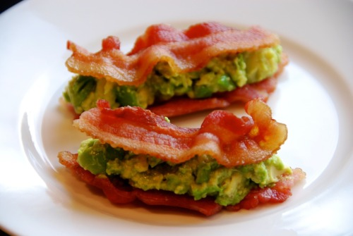 "Bacon & Guacamole SammiesDon't these bacon and guacamole sammies look good? Fitbomb noshed on them while I slept…The ingredients:4 strips of thick-cut pastured baconGuacamoleIt's ridiculously easy to cook bacon in the microwave oven. (Clean-up is simple, too.) Just wrap a few slices between some sheets of paper towel, stick it all on a microwave-safe plate, and nuke away. I set my microwave at 70% power and zapped the bacon for about two-and-a-half minutes. If you find that your bacon's not yet crisp, just nuke it a bit longer.  The filling for these ""sandwiches""? Chunky homemade guacamole.  If you're pressed for time, simply mash up the flesh of half an avocado, and cut up the other half into half-inch cubes. Then mix both halves together in a bowl to get a nice blend of chunky 'n creamy. Flavor it with a squirt or two of lime juice and a generous pinch of Kosher salt.Done and done!"