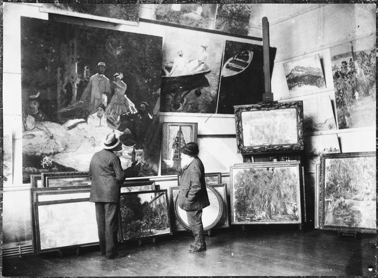 Monet in his studio with the Duke of Treviso looking at the central part of the Luncheon on the Grass in 1920. via