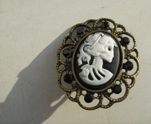 Brass frame, resin cameo, butterfly pin back, black matte rhinestones.This is a gothic essential which will add a touch of morbid class to any outfit - monochrome or otherwise. Perfect on blazers, collars, and even t-shirts.