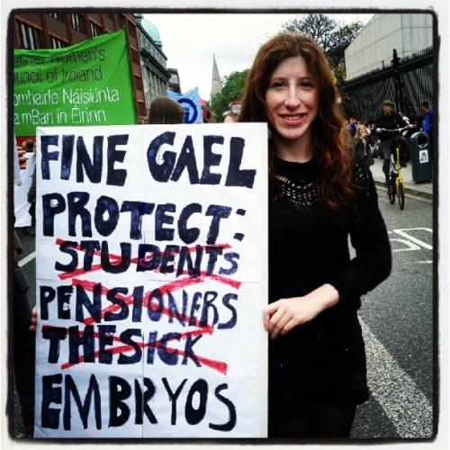 "Woman carrying a sign saying ""Fine Gael protects..."" then with the words ""Students, Pensioners, the Sick"" crossed out, and then the word ""Embryos"""