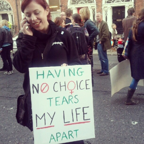 "Woman on the phone, holding a sign saying ""Having no choice tears MY life apart"""