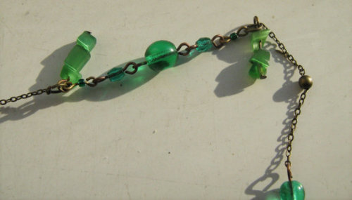28 inch / 71 centimetre brass chain, acrylic and glass bead necklace with brass filigree beads.A dainty but eye-catching combination of vivid green and deep brass, this delicate mid-length confection is perfect paired with long or short necklaces, and makes a subtle statement when worn alone.