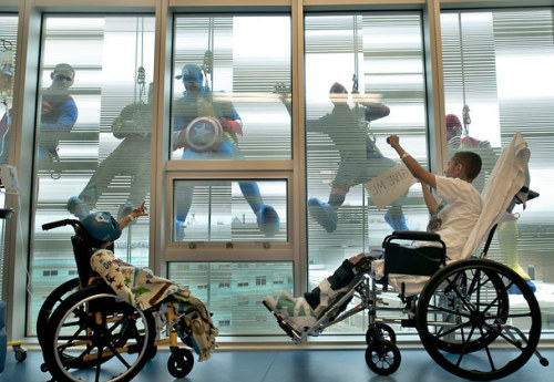 Two children in wheelchairs are waving at abseiling men outside a huge window.  The men are wearing superhero costumes.