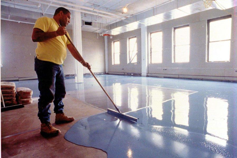 Basement Floor Paint   Epoxy Basement Floor   ArmorPoxy     man in yellow applies blue epoxy paint to basement floor