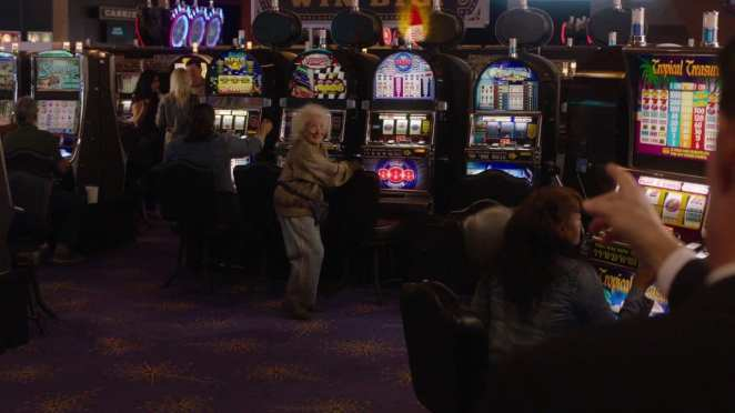 an old woman wins the jackpot at a casino while Agent Cooper points at the fruit machine she's playing
