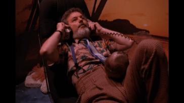 Dr Jacoby lies on a sofa with headphones on