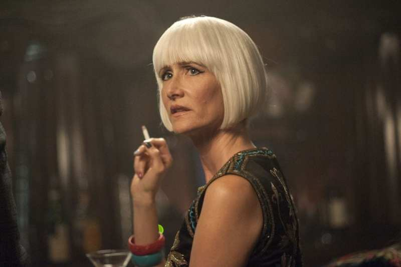 Diane sits at a bar with a martini and cigarette, her hair in a platinum bob. Played by Laura Dern