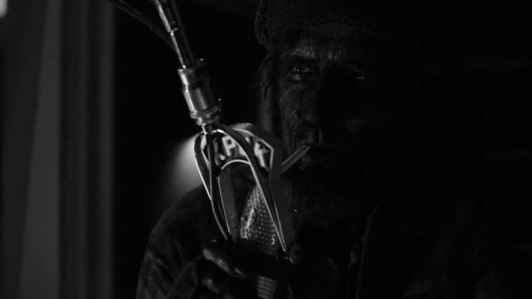 woodsman talking into a radio mic with cigarette in mouth