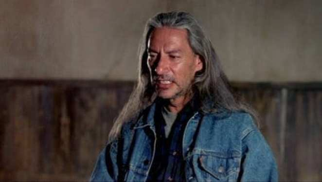 BOB in the convenience store dressed in a denim jacket with scraggy long grey hair