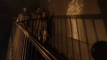 3 dark woodsmen stand at the top of a dirty staircase