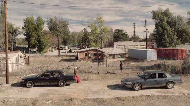 2 cars parked outside a pink bungalow with Diane, Tamara Preston, Gordon Cole and Albert Rosenfield standing outside