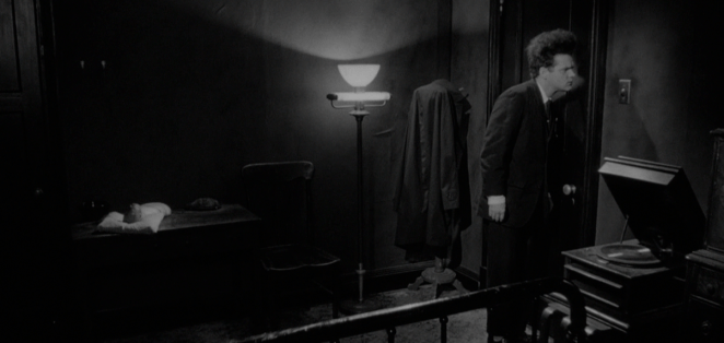 Henry in Eraserhead next to a record player, listening at the door