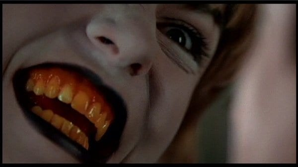 laura palmers face is white with black lips and yellow teeth