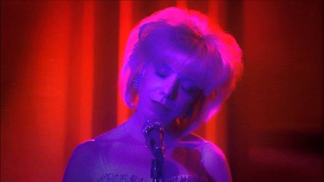 julee cruise sings lit in blue light with red curtains behind her