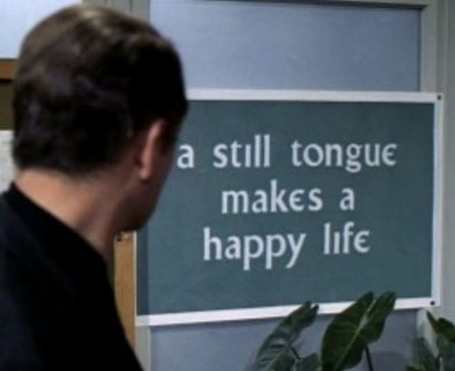 The prisoner reads a sign that says A Still Tongue Makes a Happy Life