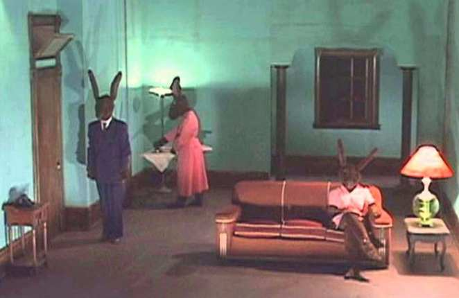 Rabbits short film by David Lynch, shows 3 rabbits in clothes in a house, one ironing, one watching tv, the other standing straight