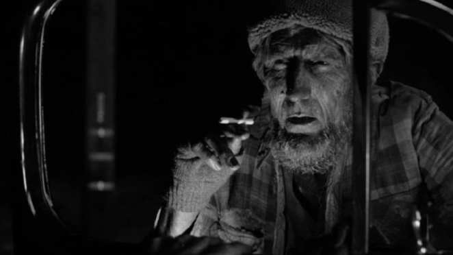 Robert Broski as a Woodsman asks through a car window for a light for his cigarette