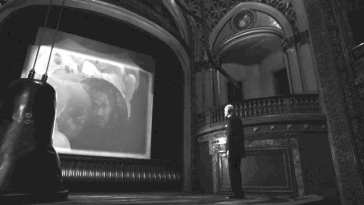 The Fireman watches a screen in a black and white theater