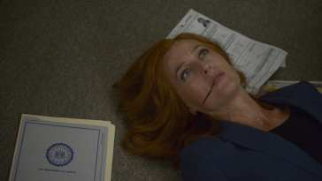 Scully lies on the floor having been attacked