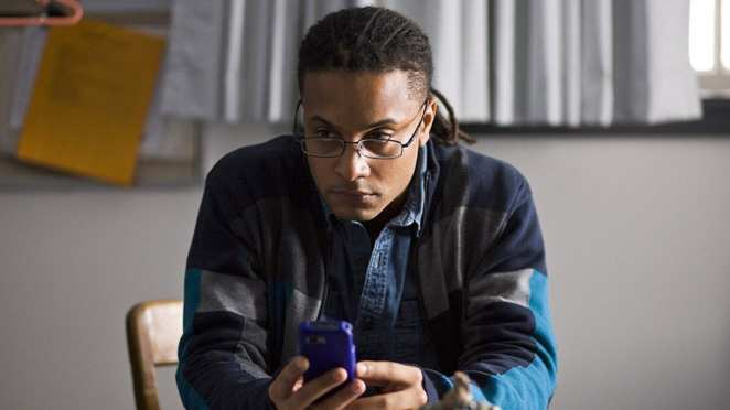 Brandon Jay McLaren as Bennet Ahmed texting on his phone in The Killing