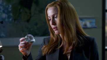 Dana Scully looks sadly into a snowglobe