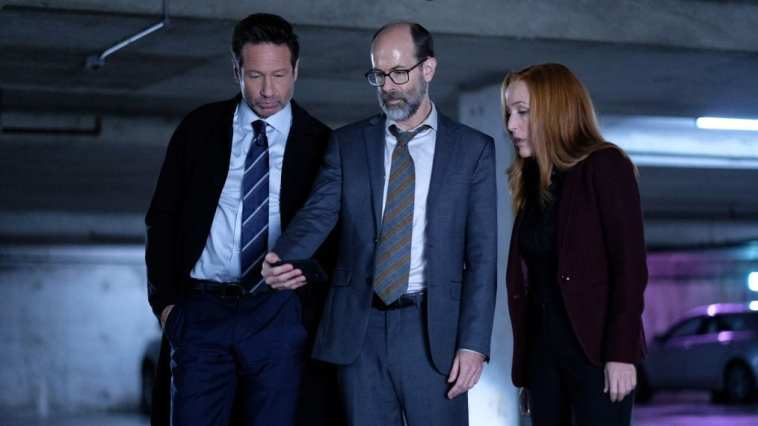 Mulder, Scully and a man look at a cell phone in a parking lot