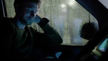 Ash sits in a car with rain on the window