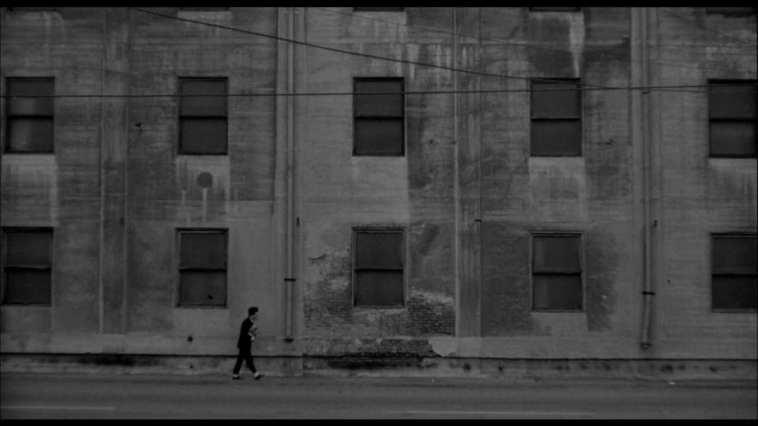 Ronnie Rocket walks past a huge grey building
