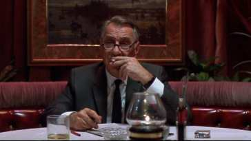 Phillip Baker Hall sits in a restaurant smoking