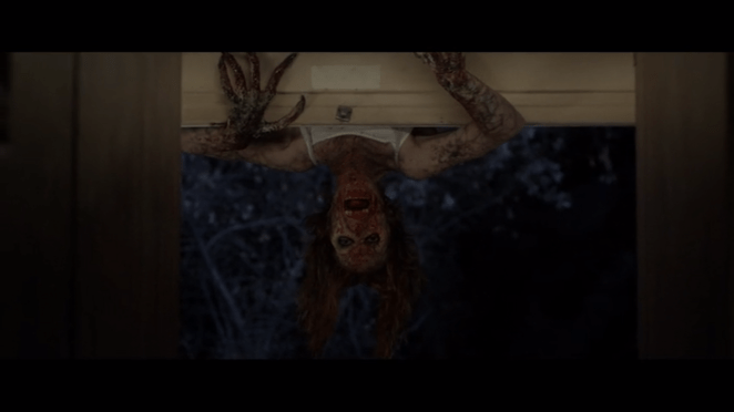 a monster human hybrid swings upside down in an open window its face covered in blood